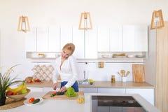 Γοητευτικό κορίτσι που μιλά στο τηλέφωνο και την προετοιμασία του γεύματος στο μοντέρνο Κ Στοκ φωτογραφίες με δικαίωμα ελεύθερης χρήσης