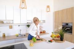 Γοητευτικό κορίτσι που μιλά στο τηλέφωνο και την προετοιμασία του γεύματος στο μοντέρνο Κ Στοκ Εικόνα