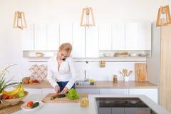 Γοητευτικό κορίτσι που μιλά στο τηλέφωνο και την προετοιμασία του γεύματος στο μοντέρνο Κ Στοκ εικόνες με δικαίωμα ελεύθερης χρήσης