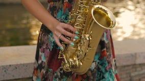 Γοητευτικό κορίτσι που παίζει το saxophone κοντά στη λίμνη στο ηλιοβασίλεμα φιλμ μικρού μήκους