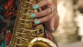 Γοητευτικό κορίτσι που παίζει το saxophone κοντά στη λίμνη στο ηλιοβασίλεμα απόθεμα βίντεο