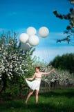 Γοητευτικό κορίτσι σε μια πράσινη περιοχή που έχει τη διασκέδαση στοκ εικόνα