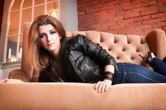 Γοητευτικό κορίτσι στο σακάκι δέρματος με τις υψηλές αντλίες που βρίσκονται σε έναν καναπέ Στοκ Φωτογραφίες