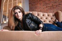 Γοητευτικό κορίτσι στο σακάκι δέρματος με τις υψηλές αντλίες που βρίσκονται σε έναν καναπέ Στοκ Εικόνες