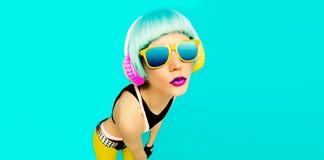 Γοητευτικό κορίτσι του DJ κομμάτων στα φωτεινά ενδύματα σε ένα μπλε υπόβαθρο λ Στοκ Εικόνες