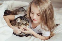Γοητευτικό μικρό κορίτσι που αγκαλιάζει τη γάτα της Στοκ Φωτογραφίες
