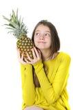 Γοητευτικό νέο κορίτσι που κρατά έναν μεγάλο ώριμο ανανά και που φαίνεται το u στοκ φωτογραφία με δικαίωμα ελεύθερης χρήσης
