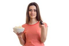 Γοητευτικό νέο κορίτσι που χαμογελά και που κρατά pop-corn και το μακρινό από τη TV Στοκ εικόνα με δικαίωμα ελεύθερης χρήσης