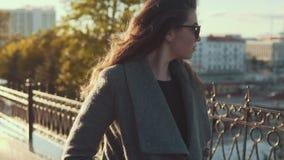 Γοητευτικό νέο κορίτσι στους περιπάτους γυαλιών ηλίου μέσω της πόλης φθινοπώρου στο παλτό απόθεμα βίντεο