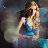 Γοητευτικό ξανθό κορίτσι σε ένα μπλε σκοτεινό υπόβαθρο φορεμάτων, κάθισμα ι Στοκ εικόνες με δικαίωμα ελεύθερης χρήσης