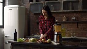 Γοητευτικό τεμαχίζοντας καρότο νοικοκυρών στην κουζίνα απόθεμα βίντεο