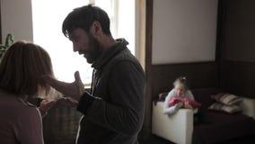 Γονείς εξαγριωμένοι και ενεργά gesticulating το κορίτσι είναι παρόν στους γονείς μιας φιλονικίας πίεση σε ένα παιδί απόθεμα βίντεο