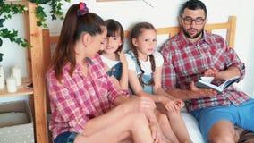 Γονείς και δύο κόρες βρίσκονται στο κρεβάτι και ο μπαμπάς διαβάζει το βιβλίο σε τους, σε αργή κίνηση απόθεμα βίντεο