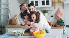 Γονείς και δύο κόρες που μαγειρεύουν στην κουζίνα, αγκαλιάζουν και γελούν, σε αργή κίνηση απόθεμα βίντεο