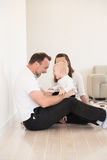 Γονείς και η όμορφη συνεδρίαση κοριτσάκι τους στο έδαφος και παιχνίδι Στοκ Εικόνες