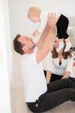 Γονείς και η όμορφη συνεδρίαση κοριτσάκι τους στο έδαφος και παιχνίδι Στοκ Εικόνα