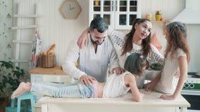 Γονείς και κόρες που λερώνονται στο αλεύρι στην κουζίνα, γέλιο, παιχνίδι, σε αργή κίνηση φιλμ μικρού μήκους