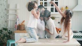 Γονείς και κόρες που λερώνονται στο αλεύρι στην κουζίνα, γέλιο, παιχνίδι, σε αργή κίνηση απόθεμα βίντεο