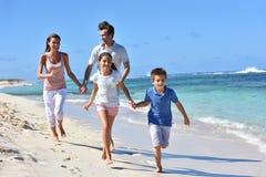 Γονείς και παιδιά που τρέχουν στην απόλαυση παραλιών Στοκ Εικόνα