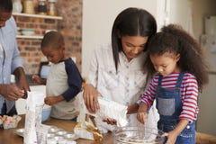 Γονείς και παιδιά που ψήνουν τα κέικ στην κουζίνα από κοινού στοκ εικόνες