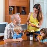 Γονείς και δύο παιδιά που έχουν το μεσημεριανό γεύμα Στοκ Εικόνες