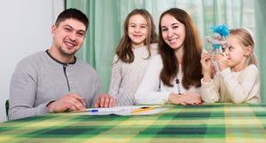 Γονείς με τα μικρά παιδιά που αγοράζουν την ασφάλεια και το χαμόγελο Στοκ Φωτογραφία