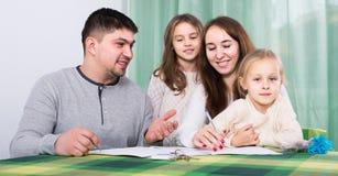 Γονείς με τα μικρά παιδιά που αγοράζουν την ασφάλεια και το χαμόγελο Στοκ Φωτογραφίες