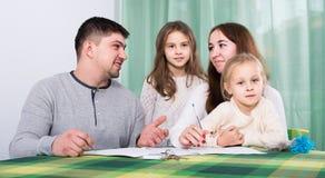 Γονείς με τα μικρά παιδιά που αγοράζουν την ασφάλεια και το χαμόγελο Στοκ εικόνα με δικαίωμα ελεύθερης χρήσης