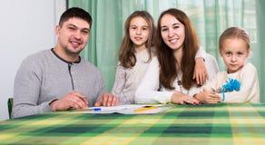 Γονείς με τα μικρά παιδιά που αγοράζουν την ασφάλεια και το χαμόγελο Στοκ Εικόνα