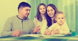 Γονείς με τα μικρά παιδιά που αγοράζουν την ασφάλεια και το χαμόγελο Στοκ εικόνες με δικαίωμα ελεύθερης χρήσης
