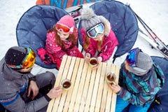 Γονείς με τα παιδιά που στηρίζονται από να κάνει σκι με το καυτό τσάι στον καφέ, Στοκ φωτογραφία με δικαίωμα ελεύθερης χρήσης