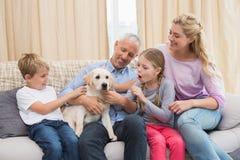 Γονείς με τα παιδιά τους στο παιχνίδι καναπέδων με το κουτάβι Στοκ Εικόνα