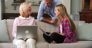 Γονείς με την ενήλικη κόρη που χρησιμοποιεί τους φορητούς προσωπικούς υπολογιστές στο σπίτι απόθεμα βίντεο