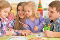 Γονείς με τις κόρες που σύρουν με τα μολύβια Στοκ Φωτογραφία