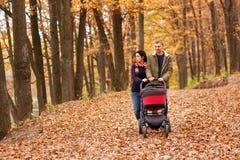 Γονείς με τον περιπατητή που περπατά στο δάσος φθινοπώρου Στοκ Φωτογραφία