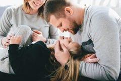 Γονείς με το γέλιο μικρών κοριτσιών στον καναπέ στοκ φωτογραφία με δικαίωμα ελεύθερης χρήσης