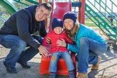 Γονείς με το παιχνίδι κορών στη φωτογραφική διαφάνεια παιδιών ` s Στοκ εικόνες με δικαίωμα ελεύθερης χρήσης