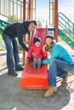 Γονείς με το παιχνίδι κορών στη φωτογραφική διαφάνεια παιδιών ` s Στοκ φωτογραφίες με δικαίωμα ελεύθερης χρήσης