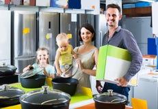 Γονείς με δύο παιδιά που επιλέγουν το σκεύος για την κουζίνα στο sto εγχώριων συσκευών Στοκ Εικόνες