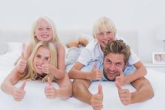Γονείς που δίνουν piggyback στα παιδιά τους δίνοντας τους αντίχειρες Στοκ Εικόνες