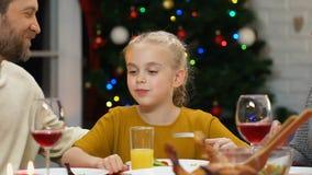 Γονείς που αγκαλιάζουν την κόρη στο γεύμα Χριστουγέννων, που απολαμβάνει την εορταστική ατμόσφαιρα απόθεμα βίντεο