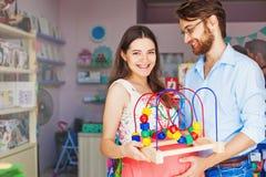 Γονείς που αγοράζουν το παιχνίδι μωρών Στοκ Φωτογραφίες