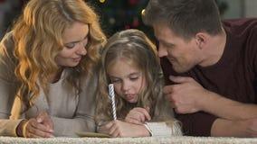 Γονείς που βοηθούν την κόρη να γράψει την επιστολή σε Άγιο Βασίλη, που χαμογελά στη κάμερα, Χριστούγεννα απόθεμα βίντεο