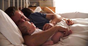 Γονείς που βρίσκονται στην αγκαλιάζοντας κόρη μωρών κρεβατιών φιλμ μικρού μήκους