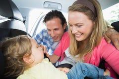 Γονείς που εξασφαλίζουν το μωρό στο κάθισμα αυτοκινήτων Στοκ Φωτογραφίες