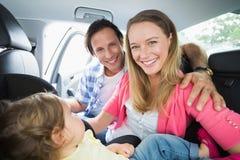 Γονείς που εξασφαλίζουν το μωρό στο κάθισμα αυτοκινήτων Στοκ φωτογραφία με δικαίωμα ελεύθερης χρήσης
