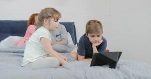 Γονείς που εξετάζουν τον κινηματογράφο προσοχής γιων και κορών στον ψηφιακό υπολογιστή ταμπλετών που βρίσκεται μαζί στο κρεβάτι σ απόθεμα βίντεο