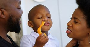 Γονείς που εξετάζουν το γιο τους τρώγοντας το πιπέρι κουδουνιών στο σπίτι 4k απόθεμα βίντεο