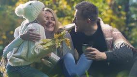 Γονείς που επικοινωνούν στο πάρκο, κόρη που παρουσιάζει τα φύλλα φθινοπώρου, που έχουν τη διασκέδαση απόθεμα βίντεο