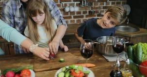 Γονείς που διδάσκουν τα παιδιά που μαγειρεύουν μαζί στην κουζίνα, ευτυχής οικογένεια που προετοιμάζει τα τρόφιμα που χρησιμοποιού απόθεμα βίντεο